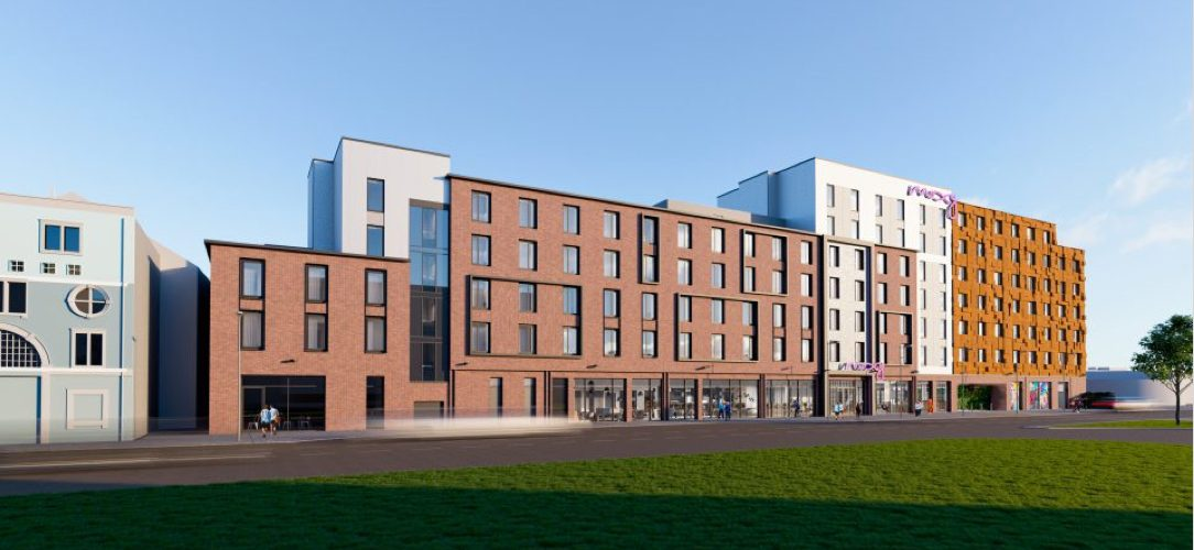 Image of new Moxy Bristol hotel taken from Newfoundland Circus, the image is an artist impression of the finished hotel set under a blue clear sky. The hotel facade is a mixture of pale cream render and red brick with framing details around the windows. The building is up to 7 stories high