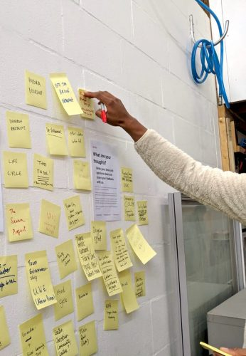 An arm reaching to attach a past-it note to all wall surrounded by other notes