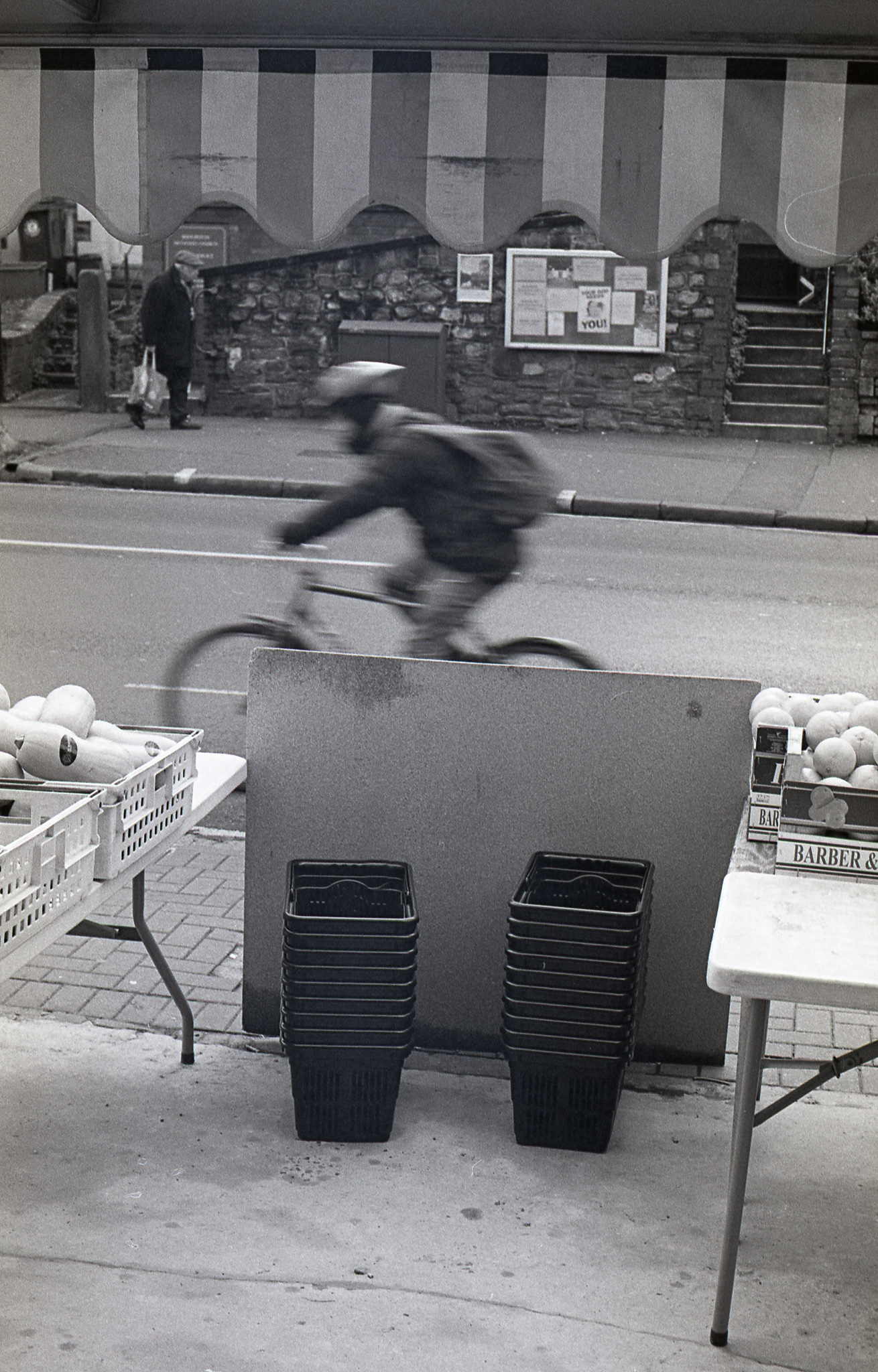 shopping baskets and fast moving cyclist with a person walking slowly in the background