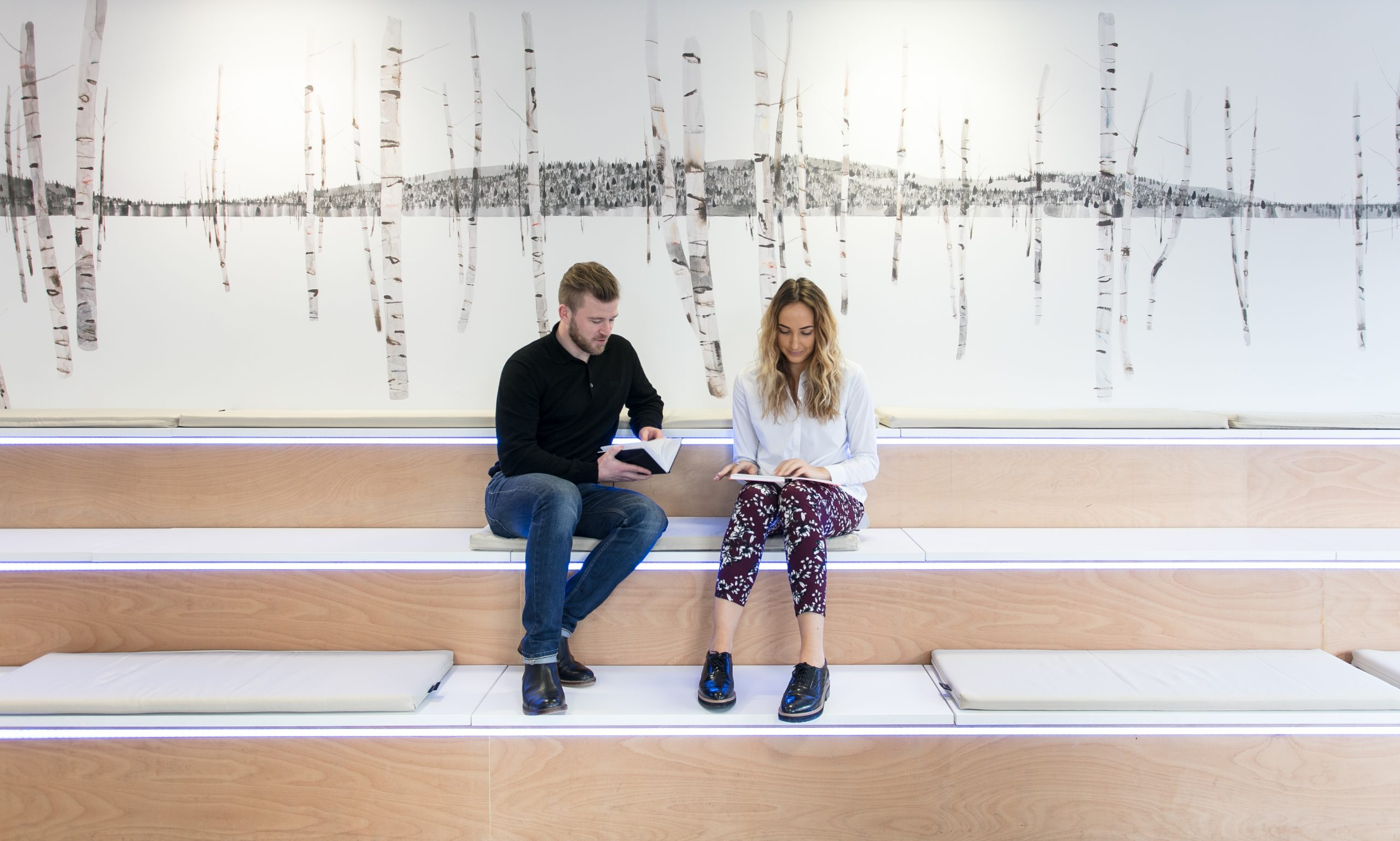 two people sat in front of beyond the birch mural