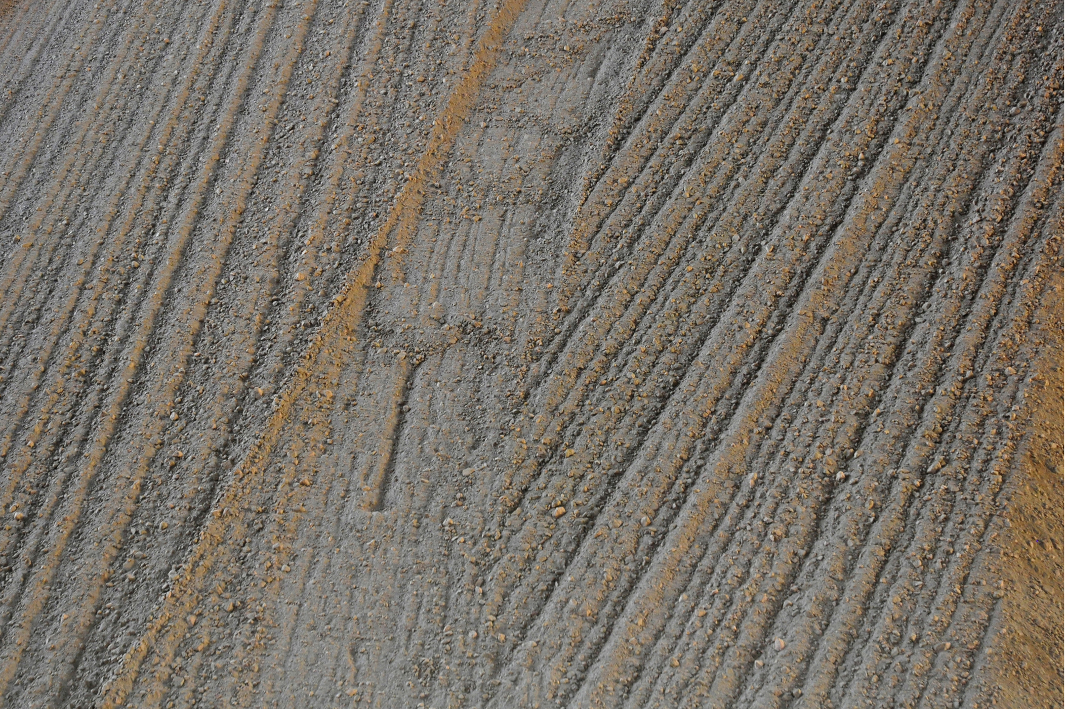a pattern of straight lined grooves in a muddy ground