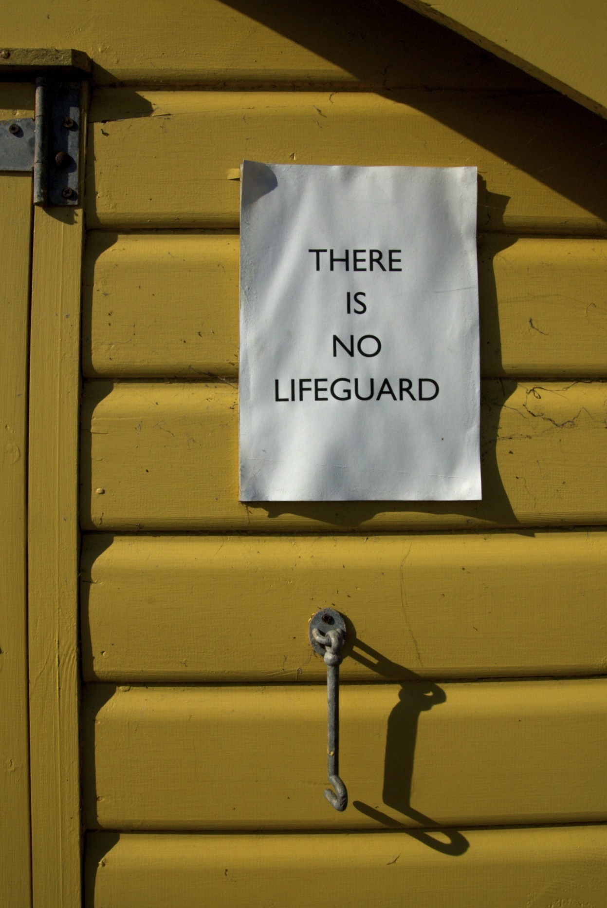 a sign which reads there is no lifeguard which is attached to a yellow beach hut