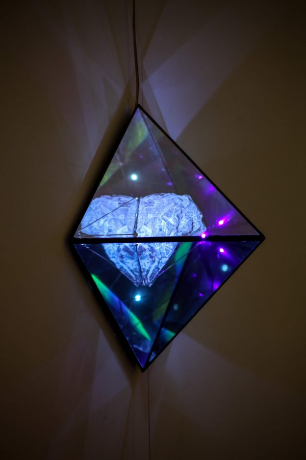 Engraved/UV painted rock, glass and mirror attached to wall with lights refracting from sculpture