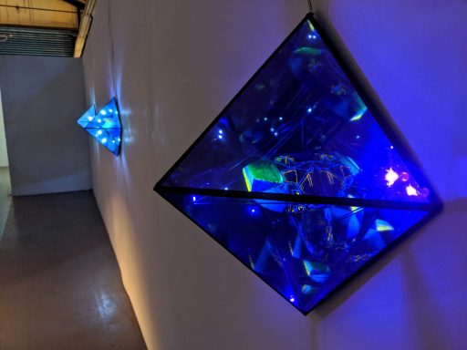 glass pyramid sculpture on wall with blue LED lights