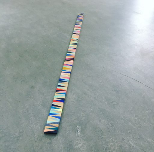 wooden plank wrapped in colourful thread