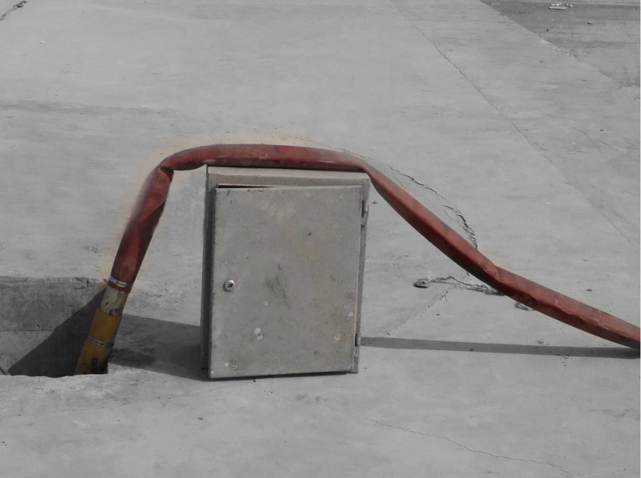 metal box with pipe laid on top of it on concrete floor