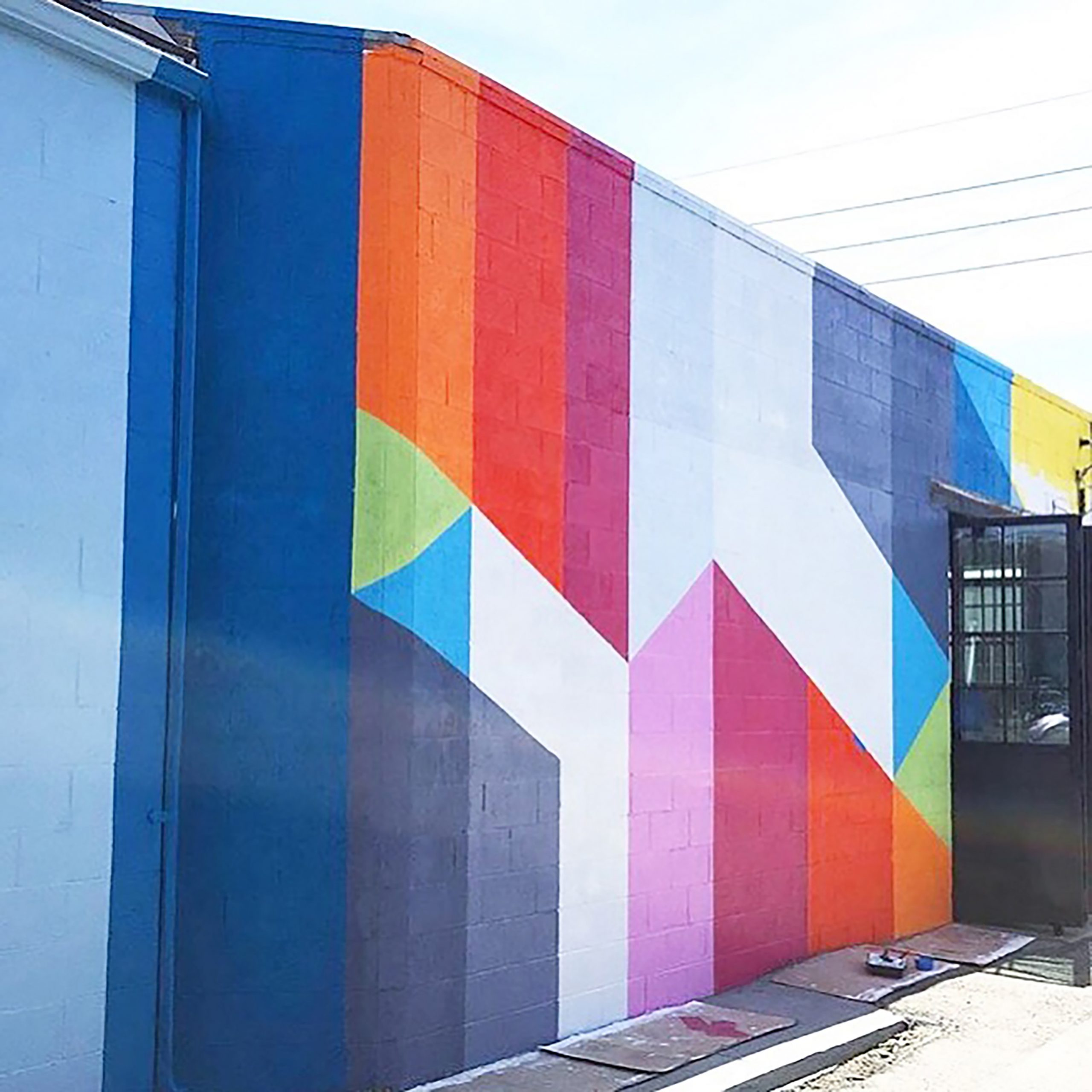 Colourful geometric striped mural covering the wall of a two story building