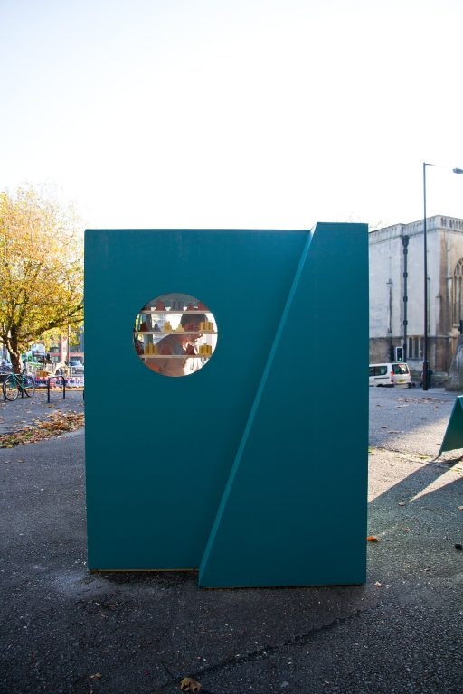 outside cuboid installation with circle window looking into the space with shelves and a person standing there