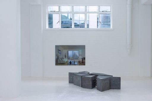 exhibition space with mirrored surface showing a contemporary sitting room also there are grey blocks collected in the middle of the room