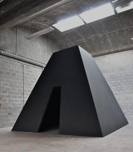 large black angular pyramid installation with an opening