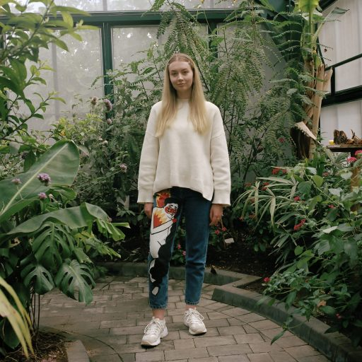 girl with cartoon graphic jeans in a green house