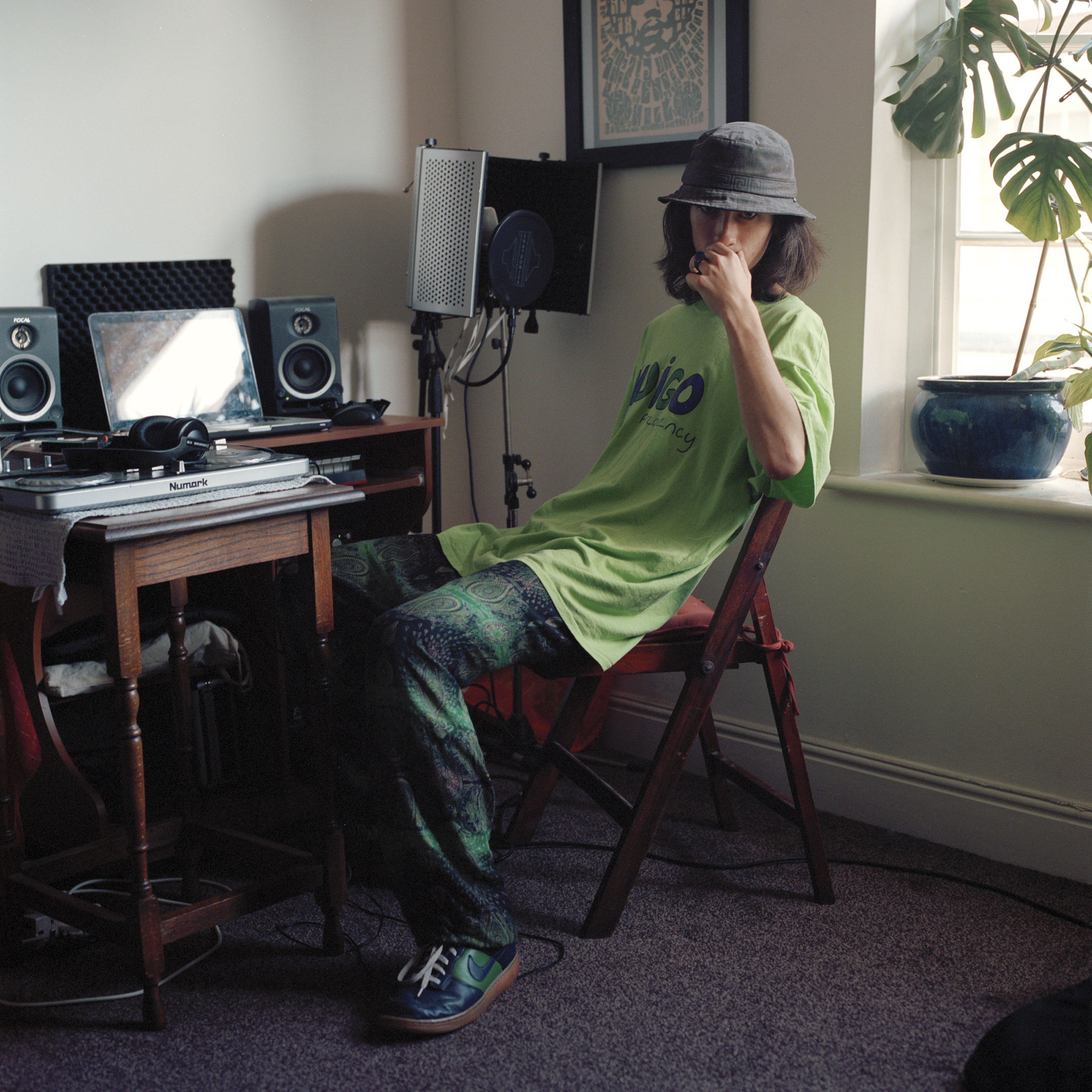 guy sat in front of a laptop and speakers wearing bucket hat and paisley trousers
