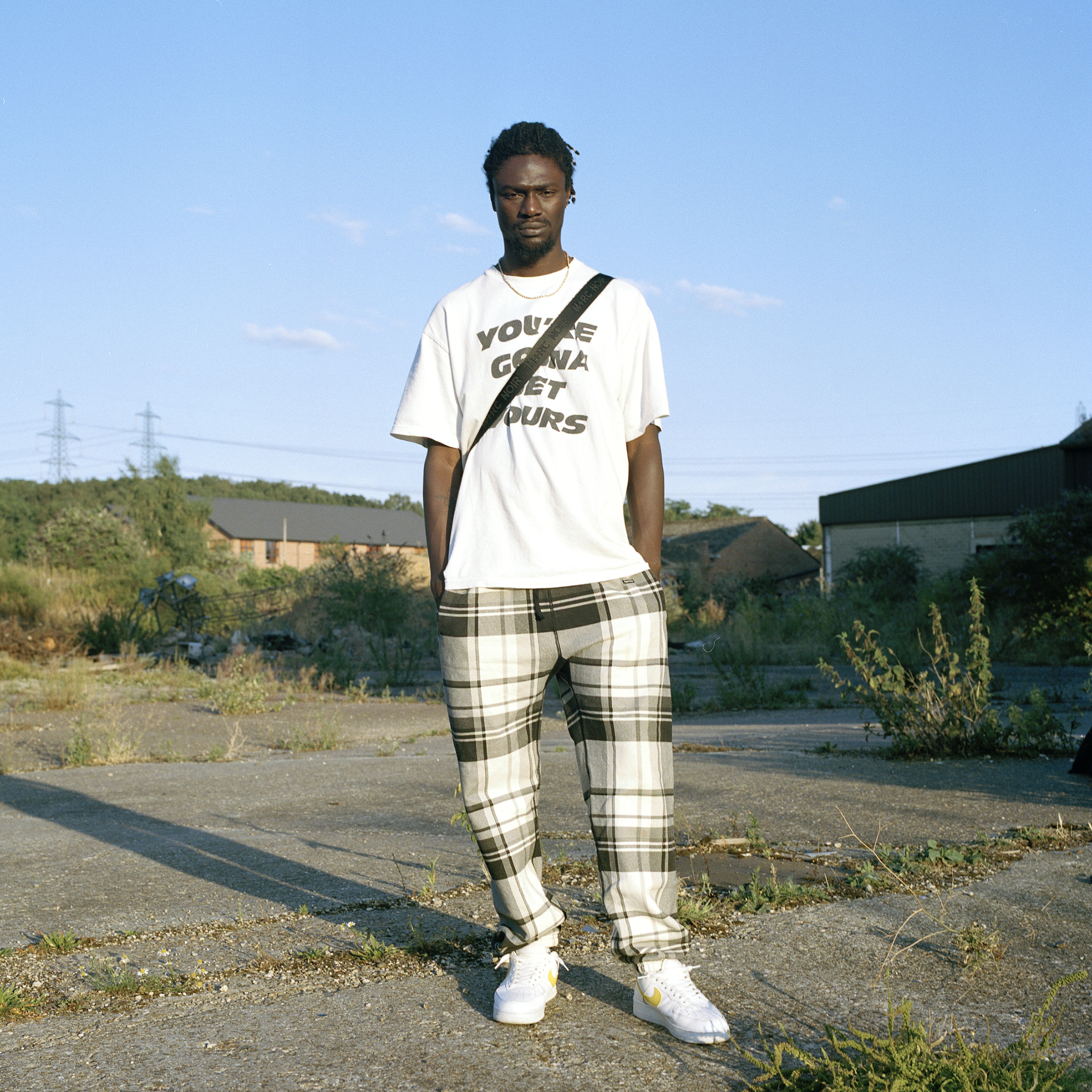 guy dressed in checked trousers in overgrown ground
