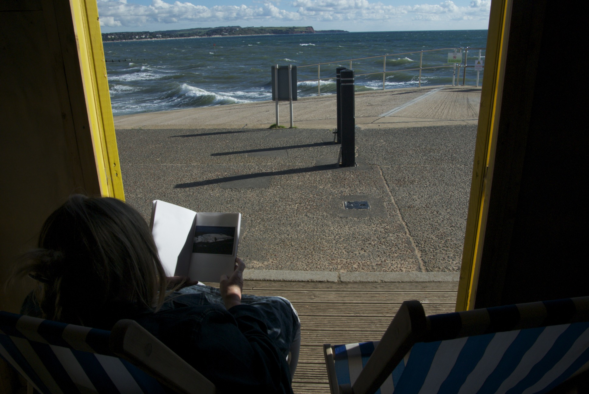 view of the seafront with choppy water from within a beach hut, across the horizon there is the edge of an island.