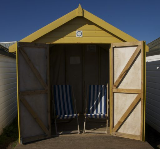 Yellow beach hut with open doors revealing two blue and white striped deckchairs
