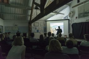 Charles Emerson Talk (Antlers at The Boat House) Photo by Damien Hockey of people sat looking a projector screen