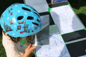 A young child looks at a map through a magnifying sheet