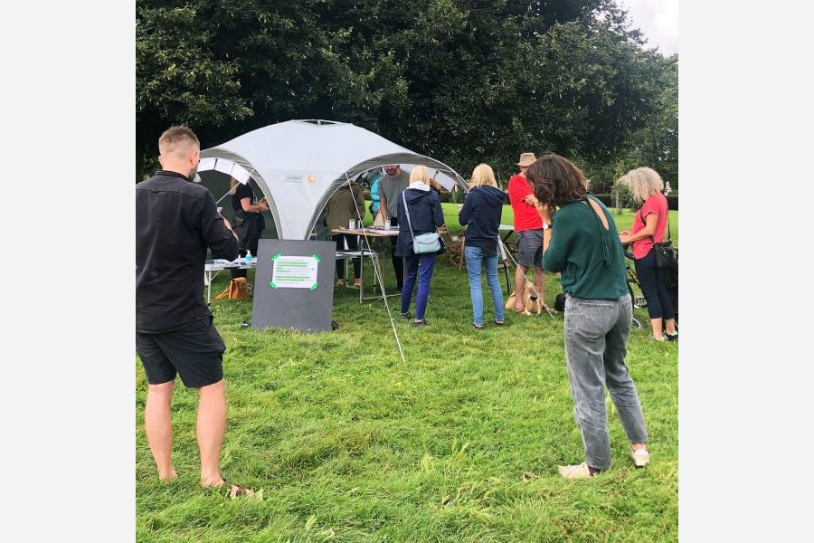 A group of people talking whilst in and around a tent on the grass