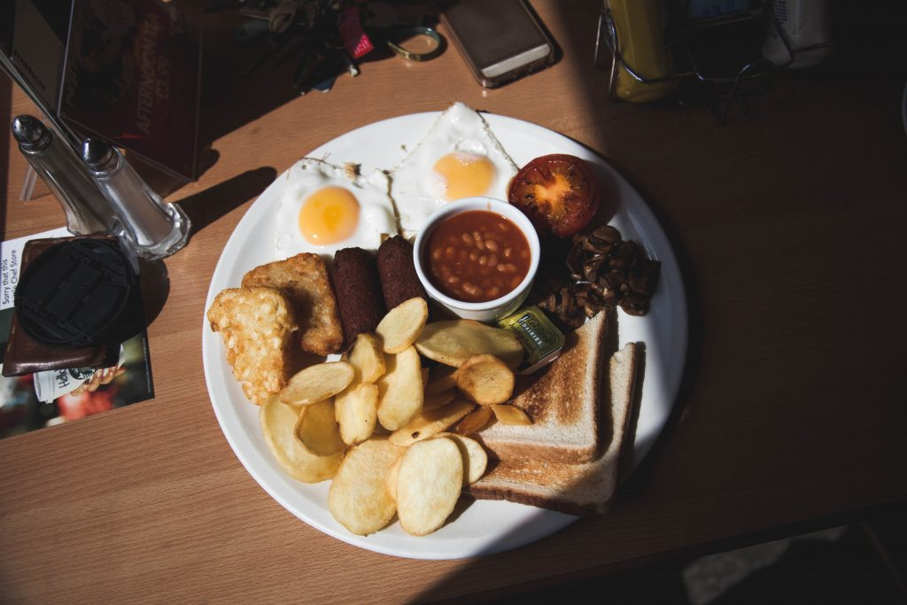 White plate of fried food on table with sun shining on it.