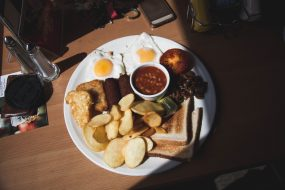 Fried breakfast on white plate on table in sun.
