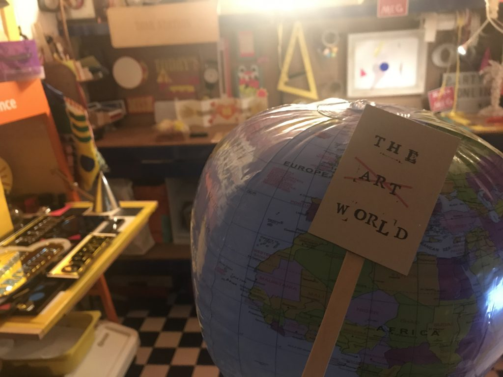 Blow up globe in studio surrounded by tools. Small placard leans on globe saying The Art World with Art crossed out.