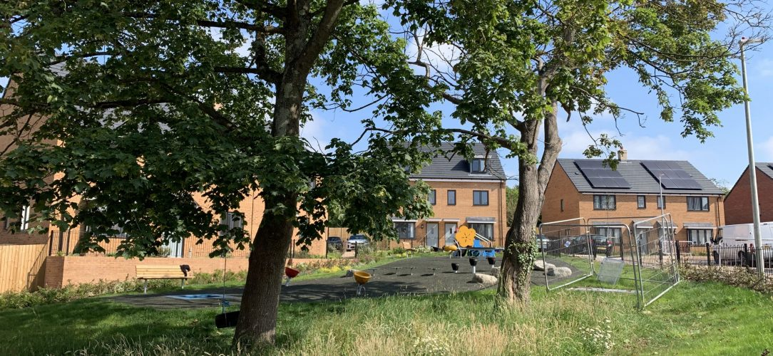 Roseneath Gardens, Stoke Gifford playground with two mature trees and new houses beyond