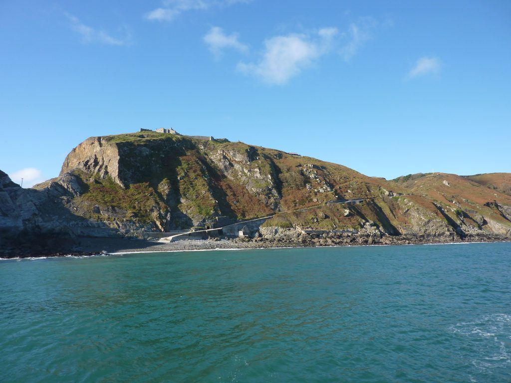 Picture of a calm sea and rocky cliffs with a path that cuts diagonally up across it from the beach to the top.