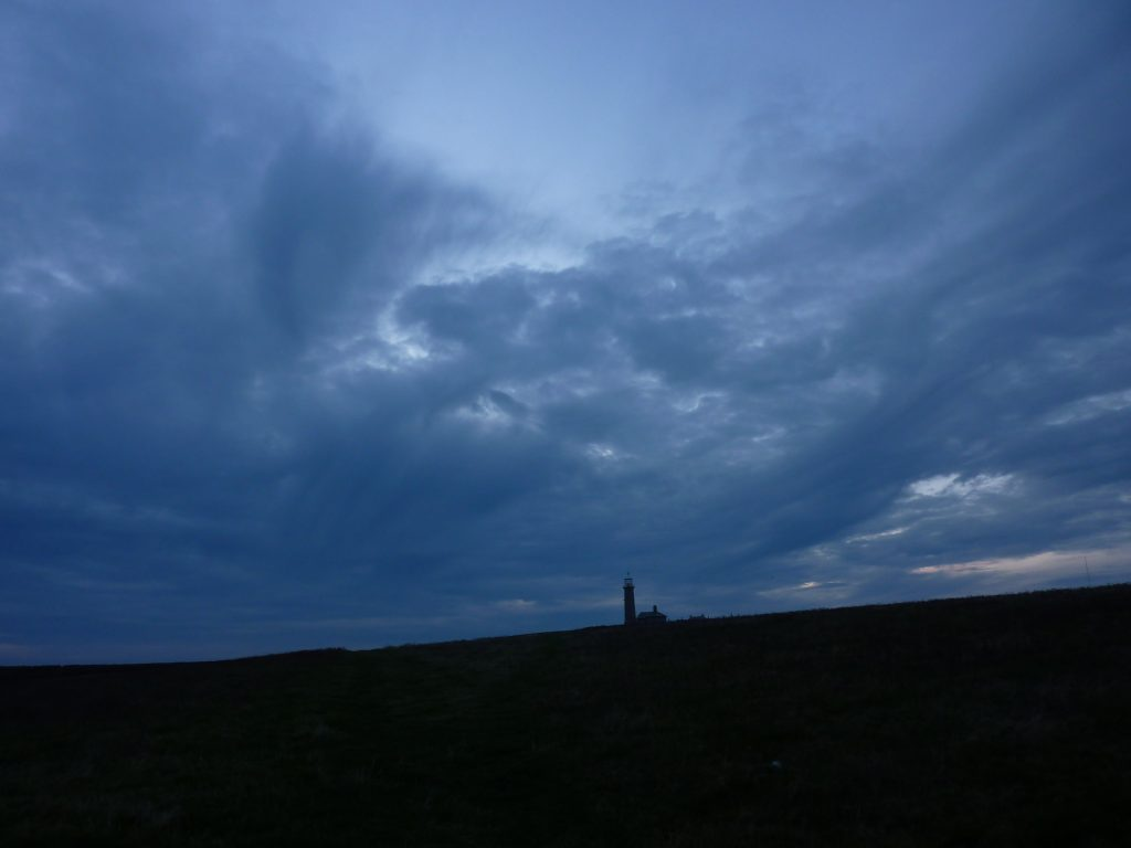 Picture of a dark landscape lighthouse silhouetted on the horizon with swirling clouds overhead