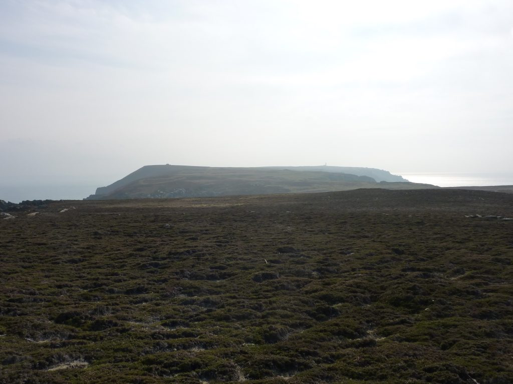 Picture of a wide moor like landscape with two buildings in the far distance and the sea either side