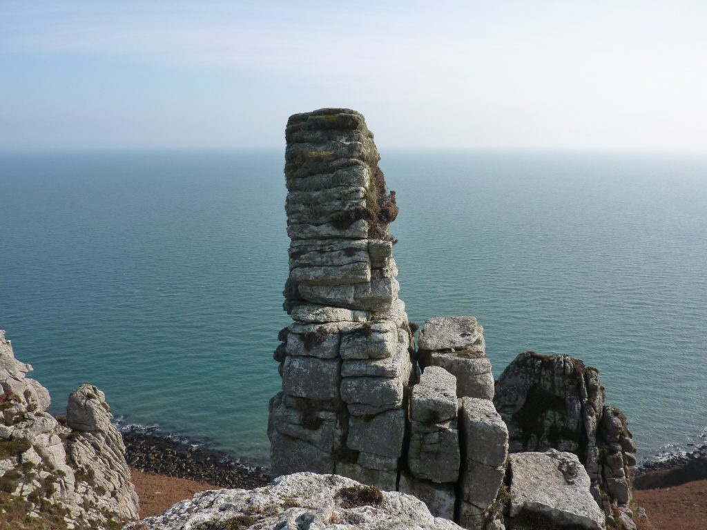 Picture of a stacked granite rock formation with the sea in the background