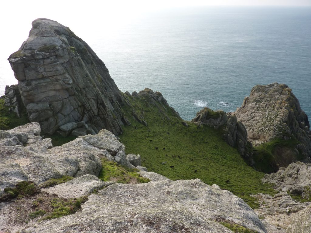 Picture of two large rock formations with a grassy bank dotted with goats in between and the sea in the background