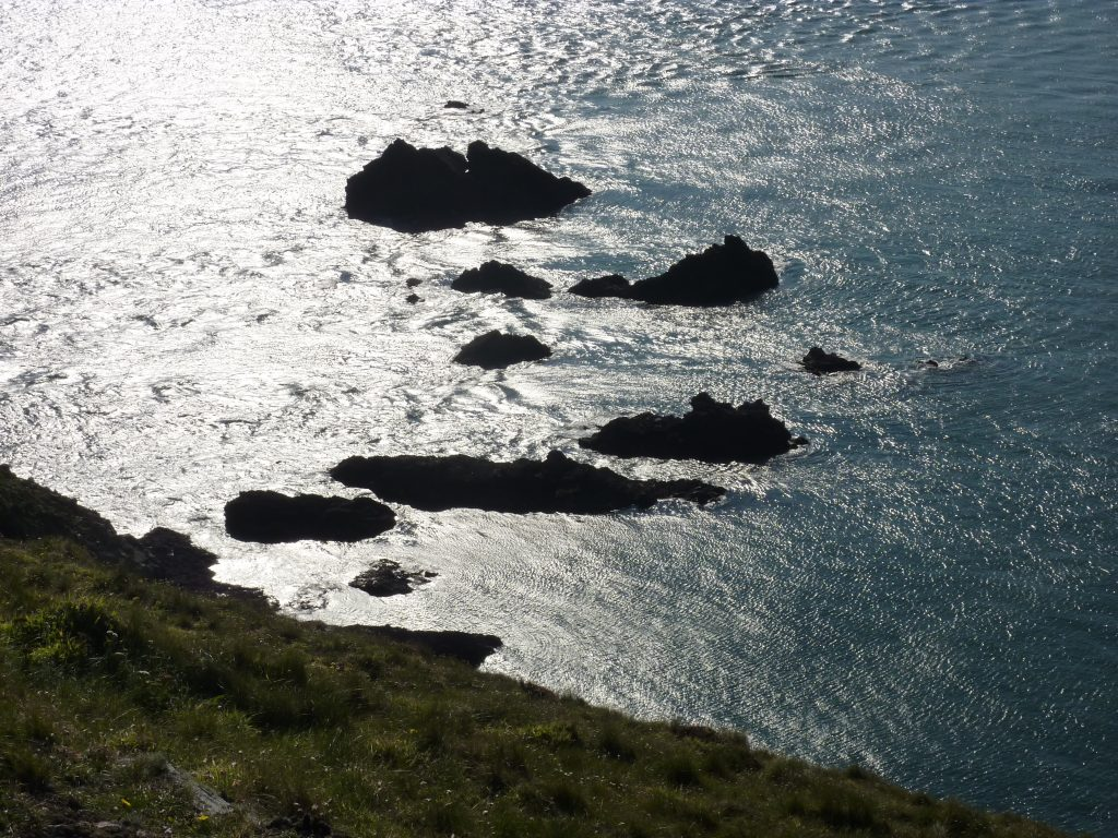 Picture of shadowy rock formations emerging from the sea