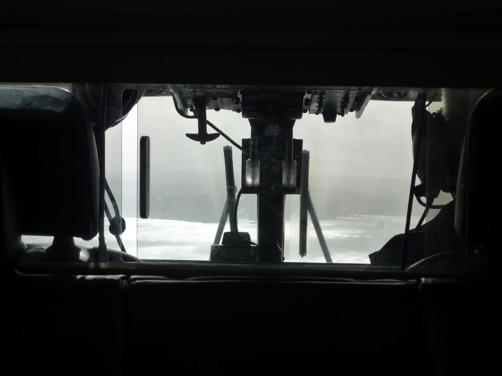 Picture of the inside of a helicopters cockpit looking out to the sea and a coastline on the horizon