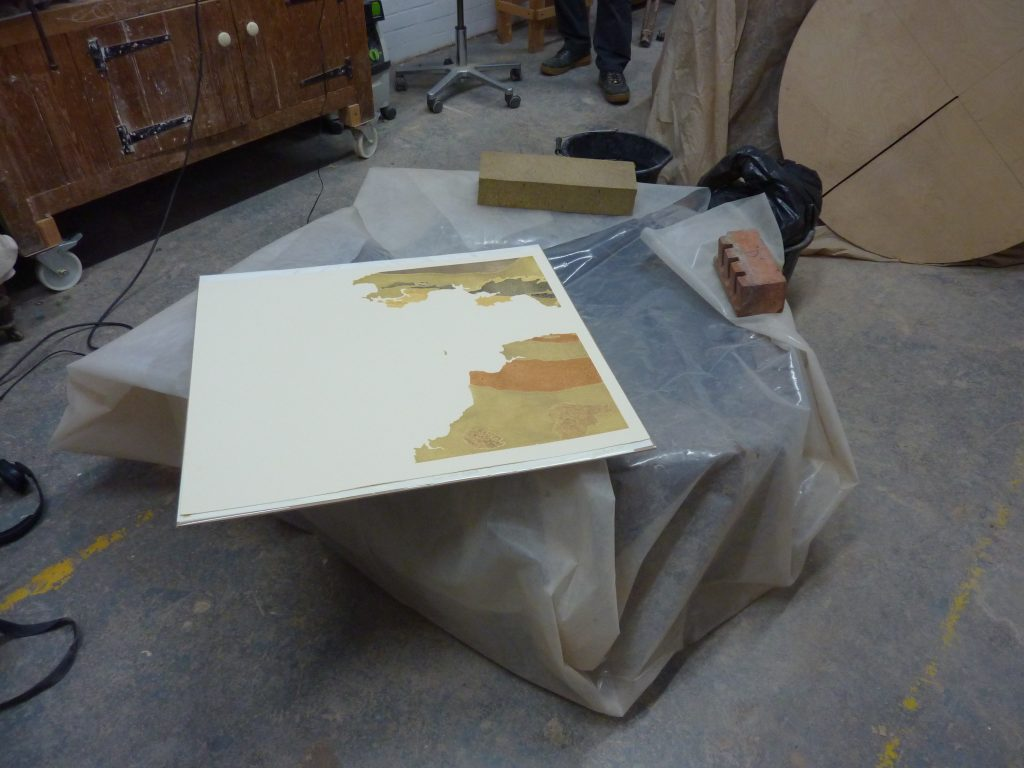 Photograph of a geological print out laid out low to the ground in an artist's studio, the artist's feet are in background