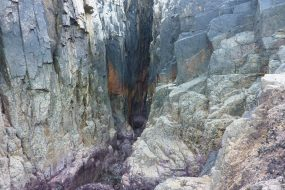 Picture looking into a rocky cave recess from sea level