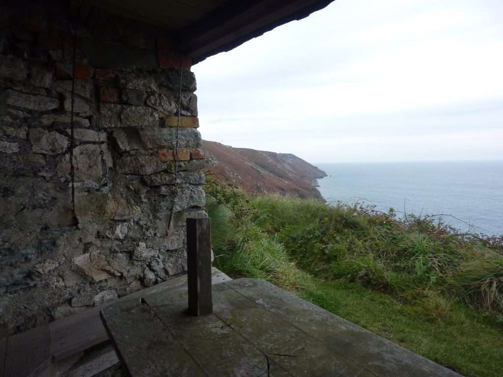 Photograph taken from inside a stone shelter looking out to a rocky coastline covered in foliage and the sea
