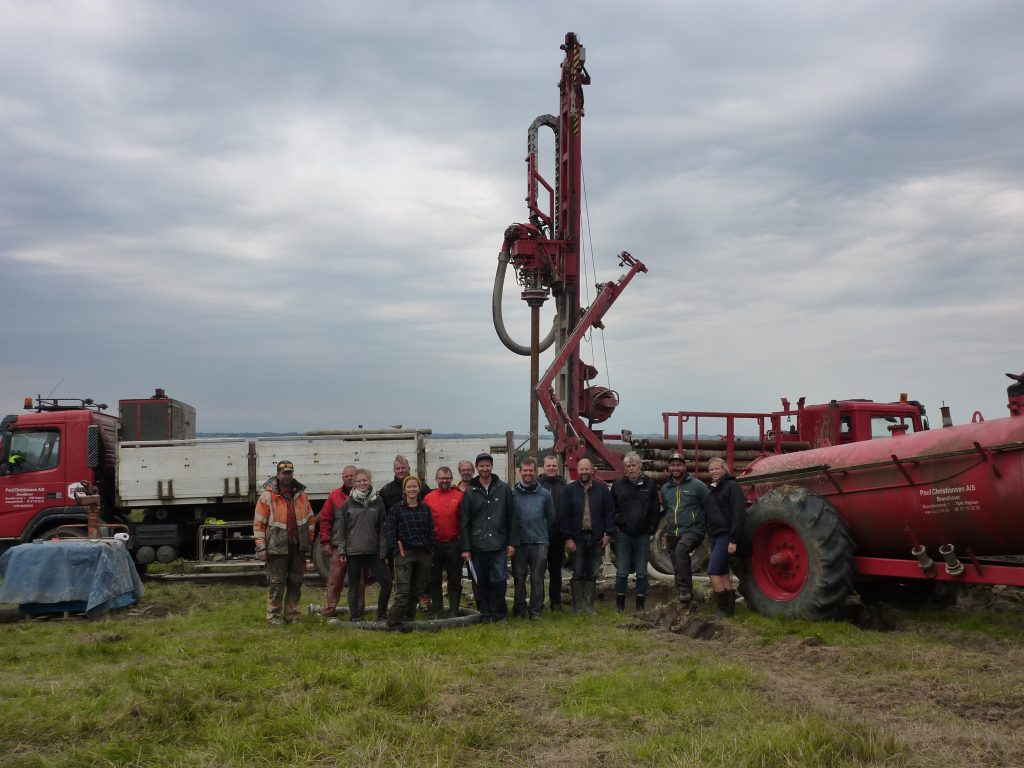 Image of a group of 14 people lined up for a photo in a field in front of a core digging machine.