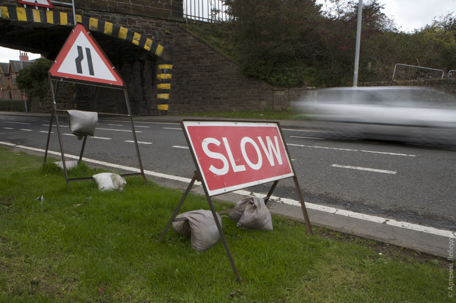 Roadside sign saying SLOW on grass verge beside low bridge with silver car blurred passing by.