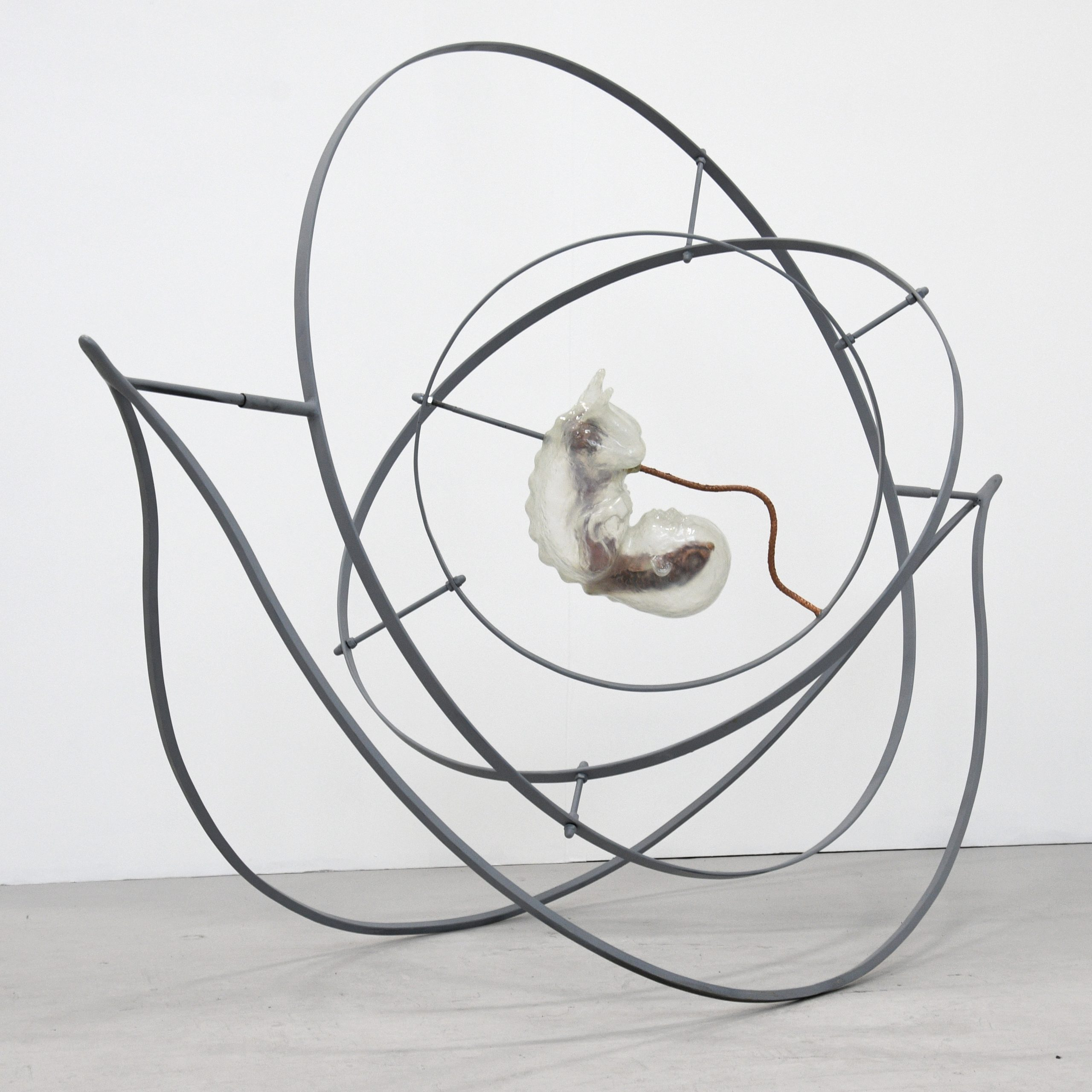 A metallic sculptural piece. It is reminiscent of a double helix. A foetal figure sits in the centre.