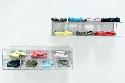 Like bricks, seven perspex boxes are stacked on a wall with latex bodysuits that are in varying pastel shades, such as pale yellow, coral, lilac, light blue, as well as a dark black, green and grey. Above the stacked brick like entities there is a similar perspex shelf, and the clothes are folded onto the shelf.