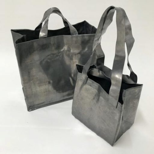 Two metallic tote bags. One is slightly larger with shorter straps. The other is smaller with longer straps. They are metal and look completely solid.