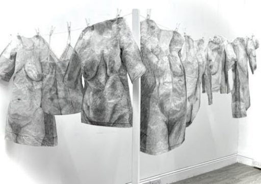 An installation piece which shows the form of a woman in grey hung up to dry like T-shirts on a laundry line.