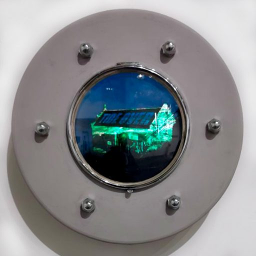 A picture of a porthole with the image of a dilapidated house at the centre of it.
