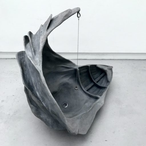 A grey sculptural floor installation. Half of the sculpture is a boat, the other half is the shape of a clam/wave.