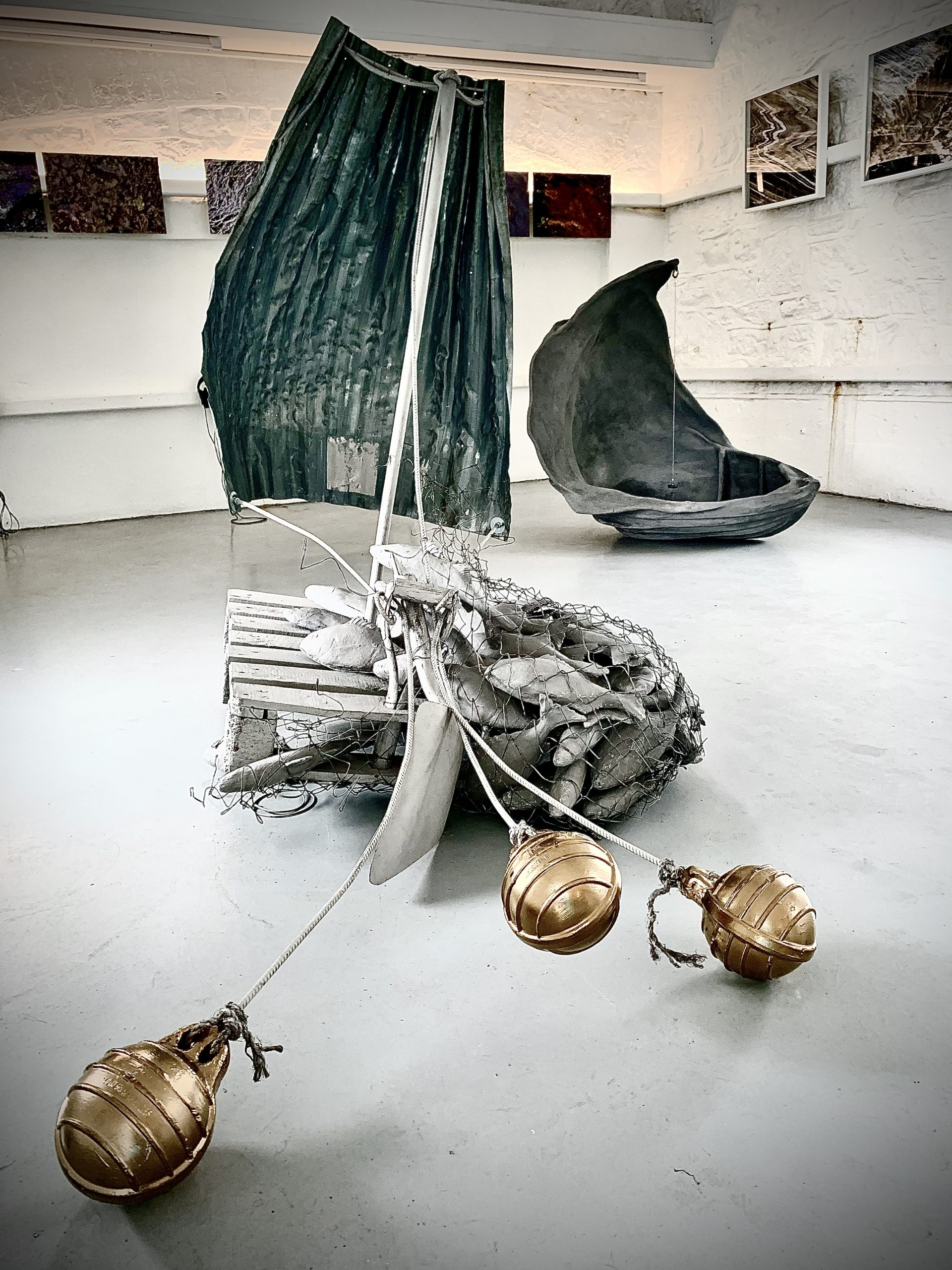 An installation floor piece which has a palette engulfed by multiple grey sculptural fish. There are gold metallic anchors petruding into the forefront of the picture.