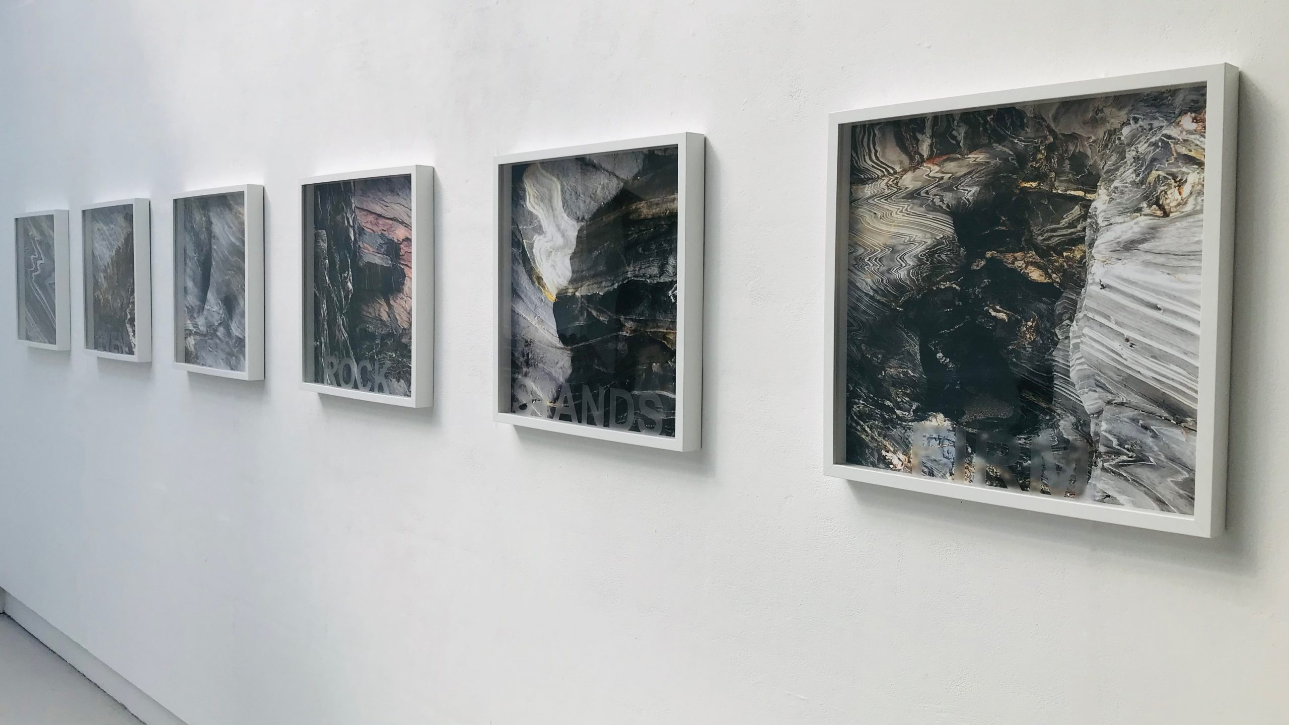 Six square framed pictures with grey, white and gold toned images of the surfaces of rocks inside them.