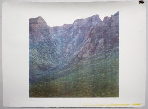 A slightly faded square photograph of a rugged mountain landscape.