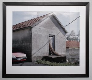 A photograph within a frame of a seemingly empty grey building.