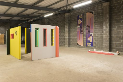 Installation shot of 3 brightly painted shop walls, wall hangings and objects.
