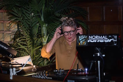 Woman in glasses at turntables with headphones on.